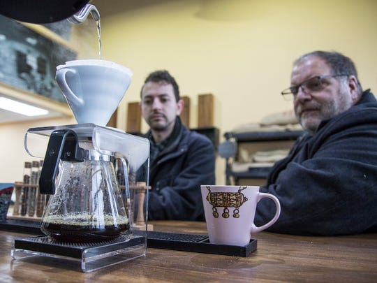 Coffee shop worker Lina Yaseen prepares a pot of pour over coffee with dark roast Yemeni coffee for Mike Pierz of Orchard Lake and Daniel Comboni of West Bloomfield. at the Qahwah House in Dearborn, Thursday, January 11, 2018.
