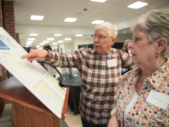 "Carol Ely of Livonia, center, and Donna Del Favero of Livonia, looks at a map that illustrates candidates district during a ""candidate speed dating"" event hosted by the Northville Democratic Club and Fems for Dems at Northville High School in Northville, Thursday, April 26, 2018."