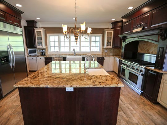 The kitchen is yet another room that runs from the front of the house to the rear. It mixes dark cherry-tone with white cabinets, upscale appliances and a huge central island.