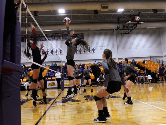 Senior Kylee Kirk spikes the ball over the net during