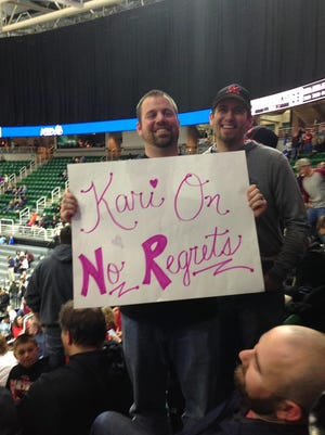 Marshall Middle School teacher Joel Jolink holds a sign featuring the mantra of his late wife, Kari Jolink, at Friday's MHSAA Class B girls basketball state semifinal. Standing behind him is Marshall Middle School assistant principal Mike Leathead.