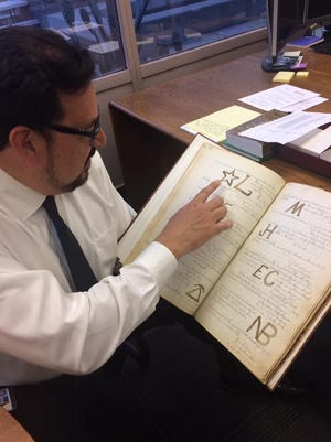 Adrian Fontes displays Arizona cattle brands from the 1870s that are kept on file at the Maricopa County Recorder's Office on Jan. 10, 2017.