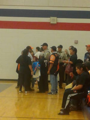 Maricopa County Sheriff's Office deputies ask Globe High School fans to move during a basketball game at the American Leadership Academy in Queen Creek.