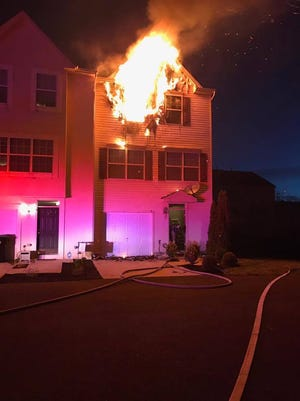Flames shoot out from a townhouse early Saturday morning on Candlestick Lane in Sicklerville.