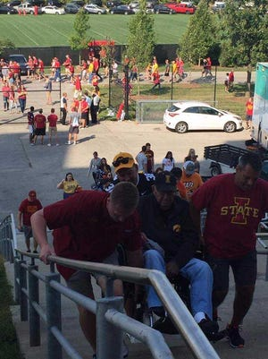 Iowa State fan Tim Hulick (right), 52, of Indianola, Ia., helps Iowa fan Max Cameron, 88, of Chariton, Ia., up the stairs outside Jack Trice Stadium on Saturday, Sept. 9, 2017, in Ames, Ia.