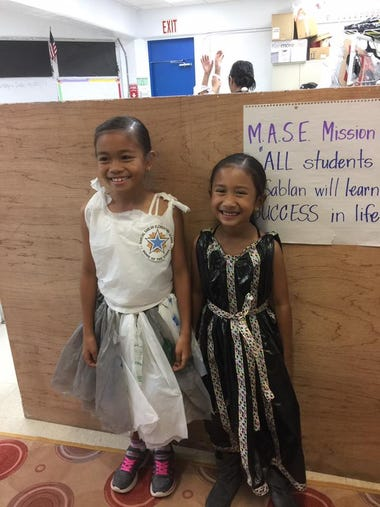 Students are all smiles as they model their recyclable