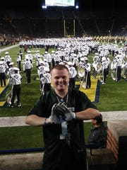 Mike Sterner aka Sparty Mike smiles and poses in front of the Michigan State band during the MSU-Michigan game Oct. 7 in Ann Arbor.