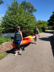 Alexis Buckley and Nick Buckley carry a kayak down to the launch site near the Kellogg House.