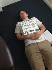 """Summit High School senior Ben Schachter lies on the floor of Rep. Leonard Lance's Westfield office as part of a """"Die-in"""" protest on June 12, 2018. He was arrested after refusing to leave when the office was closed at 6 p.m."""
