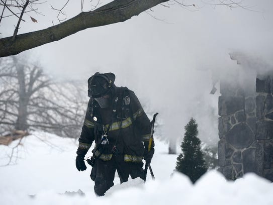 A fire fighter walks back toward a tree to take a break