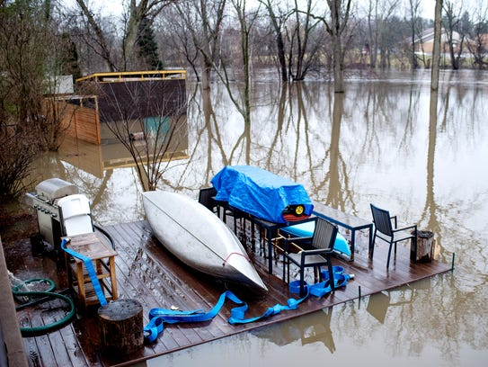 A view of Jen Estill's flooded backyard seen from her main-level porch on Friday, Feb. 23, 2018, at her home on Tecumseh River Drive in Lansing. The Grand River is usually several yards from her home.