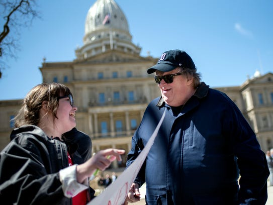 Amanda Zomberg, a senior at Coopersville High School, left, meets filmmaker Michael Moore, right, outside the Capitol on Friday, April 20, 2018, in downtown Lansing.