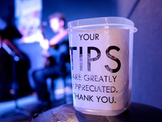 A tip jar for musicians sits on a stool near the stage