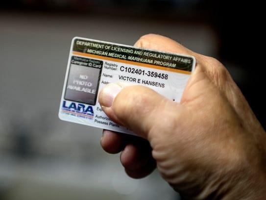 Dimondale resident Victor Hansens' displays his medical marijuana card on Friday, Nov. 17, 2017.