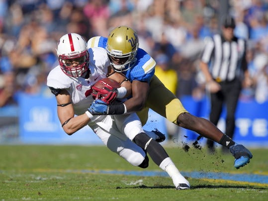 FILE - In this Nov. 28, 2014, file photo, Stanford wide receiver Michael Rector, left, is tackled by UCLA linebacker Myles Jack during the first half of an NCAA college football game in Pasadena, Calif. The UCLA Bruins feel they're still searching for national respect even after two straight 10-win seasons and a Top-10 finish last year. They're also looking for a new starting quarterback as they begin training camp practices Monday, Aug. 10, 2015, at Cal State San Bernardino in the sizzling Inland Empire. Practices are open to the public. (AP Photo/Mark J. Terrill, File)