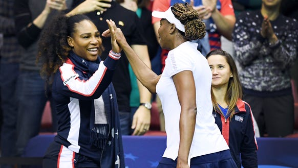 Venus Williams talks to her sister, Serena, after defeating