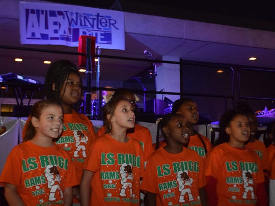 Students from L.S. Rugg Elementary School sing Christmas carols at the opening of Alex Winter Fete Thursday evening in downtown Alexandria.