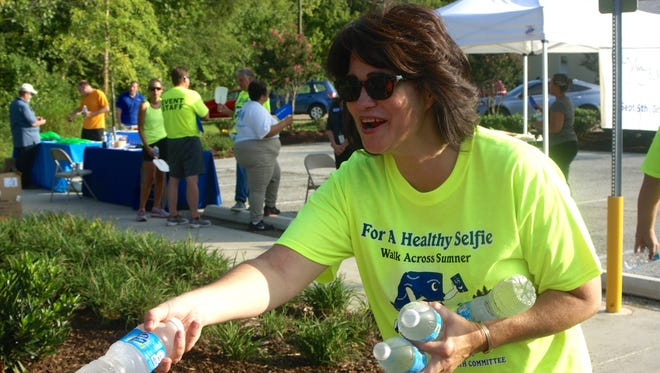 Sumner County Health Committee member Janel Garrett hands out water to walkers during Gallatin's 2014 kickoff event for the fourth annual Walk Across Sumner campaign.