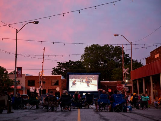 People sit along Main Street to watch Game 4 of the NHL hockey Stanley Cup Finals between the Nashville Predators and Pittsburgh Penguins as it's projected on an inflatable screen in Portland, Tenn., Monday, June 5, 2017. (AP Photo/David Goldman)