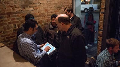 Ilyas Bourchid, general manager of the Senate in Over-the-Rhine, left, welcomes crowds into the small establishment. He uses an iPad app to add patrons to a wait list.