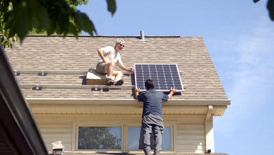 Jeremy Coxson, vice president of Sunwind Power, installed solar energy panels on the roof of Rep. Jim Wayne, with the help of Rodolfo Escamilla, last May.