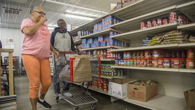 Mona Gatewood of Des Moines, left, strolls through a Des Moines food pantry.
