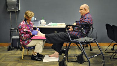Stearns County public health nurse Gail Tinglov talks with Allen Gray in October 2014 as he gets his toenails trimmed during a Senior Health Clinic at the Stearns County Service Center in Waite Park. Stearns County commissioners unanimously voted to eliminate the program