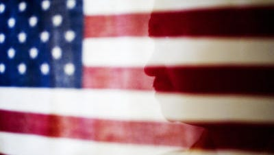 Shadow of an immigrant through the American flag