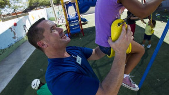 Volunteer Michael Scott pushes a child on a swing set