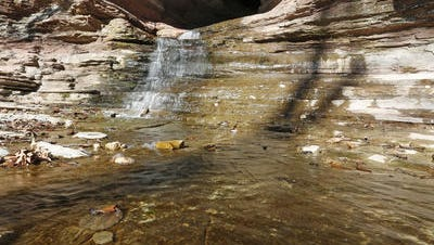 Water flows down the rocks out of the mouth of Cobb Cave along the Lost Valley trail.