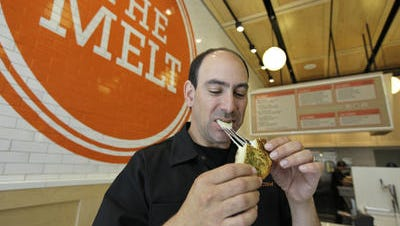 In this photo taken in 2011, Jonathan Kaplan bites into a melt called the Italian job made with fontina and provolone cheese on garlic bread at The Melt in San Franciso, the first of his grilled cheese restaurants.  Kaplan is the creator of the Flip Video camcorder.