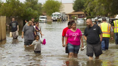 Residents and friends wade through a neighborhood near Stapley Drive and U.S. 60 on Sept. 9, 2014,   the day after floodwaters inundated their neighborhood in the Emerald Park area of Mesa.