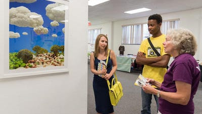 Theresa Emmett of 4Youth Productions, Jarius Branch, a student artist at 4Youth Productions, and Adele Meehan of Wilmington, discuss some art on display at an Art in the Urban Garden event at Connections in Wilmington on Saturday.