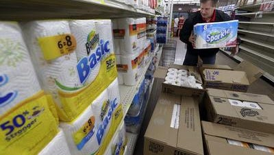 David Gaiche, a Super Valu employee, stocks paper towels at Third Street Market in Menasha in December 2014.