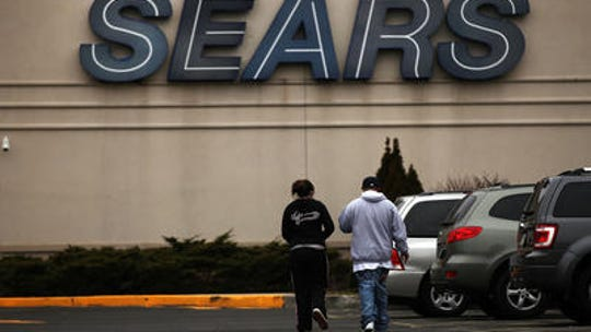 Customers walk into a Sears store.