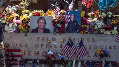 """Flowers are piled onto the memorial in front of the Palm Springs Police Department the day after officers Lesley Zerebny and Jose Gilbert """"€œGil""""€ Vega were killed. Members of Vega's church said Sunday that they kept the officers in their prayers a week after the shooting."""