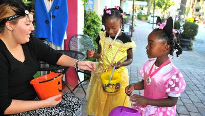 Desiree Sangster gives candy to Ty-Lasia Stewart and Arreyana Hall. Cocoa hosted Halloween in the Village in 2015