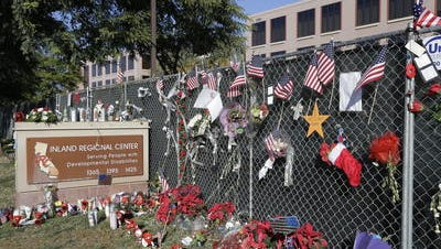 This 2015 photo shows flowers and American flags honoring the victims of the attack at the Inland Regional Center in San Bernardino. It remains under investigation one year later, according to the FBI.