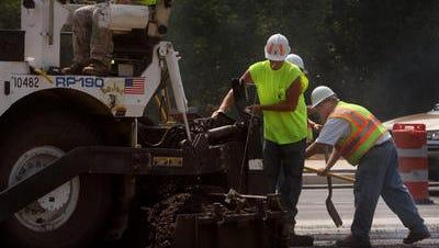 A LoJac road-paving crew lays asphalt.