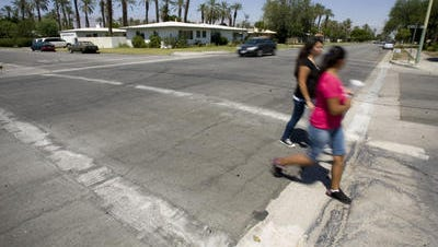 This Desert Sun file photo shows people crossing Miles Avenue and Sun Gold Street in Indio. Caltrans released a draft of its plan encouraging pedestrian and bicyclist safety.