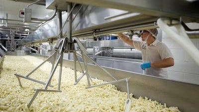 Austin Lokken, right, makes adjustments to a spinning machine inside Mullins Cheese in Mosinee, Wis.
