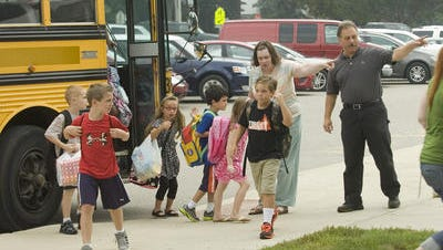 Cass Elementary School students arrive for the first day of school in September 2012. The school community is planning a 50th anniversary reunion; Cass is set to close at the end of this school year.