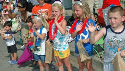 Children greet passing participants at a previous Memorial Day parade in Northville. This year's parade steps off at 10 a.m. Monday from Griswold and Main.