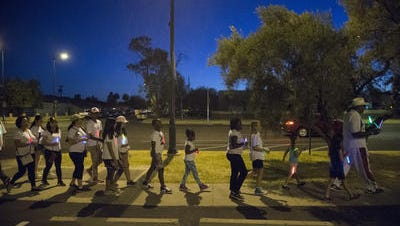 """John Goodie leads children and adults on the unity walk during the """"Light Up The Night'' event sponsored by the Mesa MLK event organizers in Mesa on June 17, 2017."""
