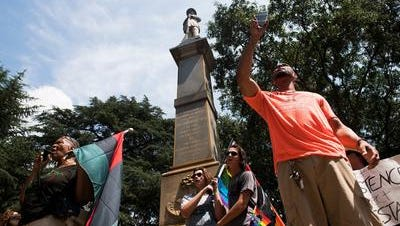 Protesters gather in front of the Confederate solider monument to call for its removal and relocation off Main Street and into a museum on Saturday, Aug. 26, 2017.
