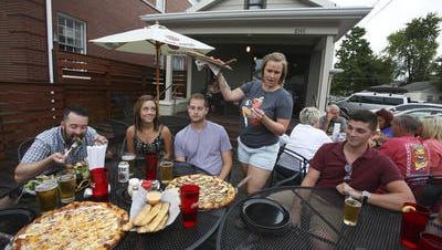 Alaina Nixon, standing, serves pizza to a group at The Post in Germantown.