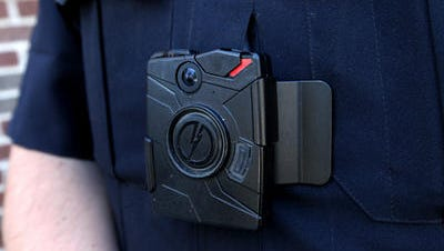 A body camera is clipped to a police officer's uniform in Lowell, Michigan