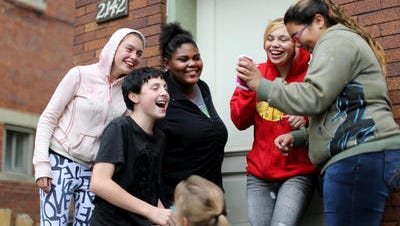 Kelsey McLean, 17, far left, hangs out with friends, including one of her best friends, Precious Gary, 16, (next to her). The group was on a front stoop on Hatmaker in Lower Price Hill, checking cell phone photos they'd taken of each other.