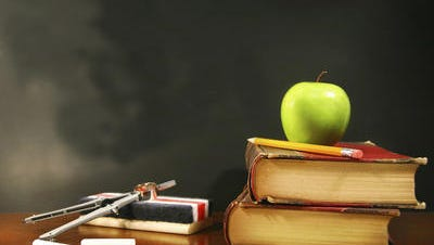 An apple sits on top of a school books.
