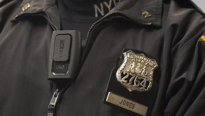 A New York City officer demonstrates a body camera.   Problem solver? No. But it will help.